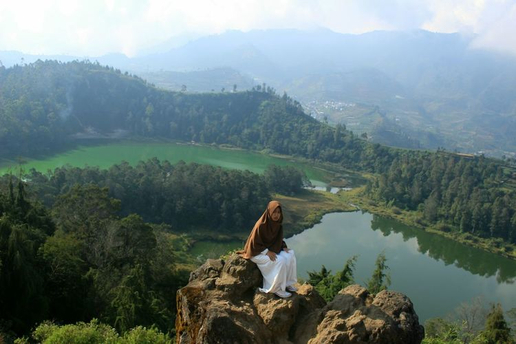 Woman sitting on mountain by mountains with lake background