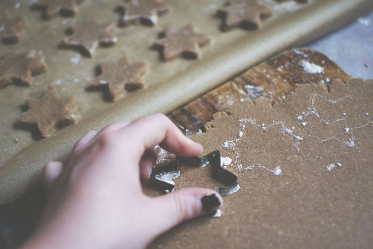Cropped hand of woman making star shape cookie on table