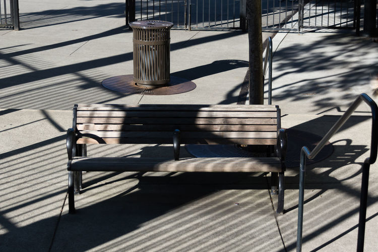 High Angle View Of Shadow Falling On Empty Bench At Footpath