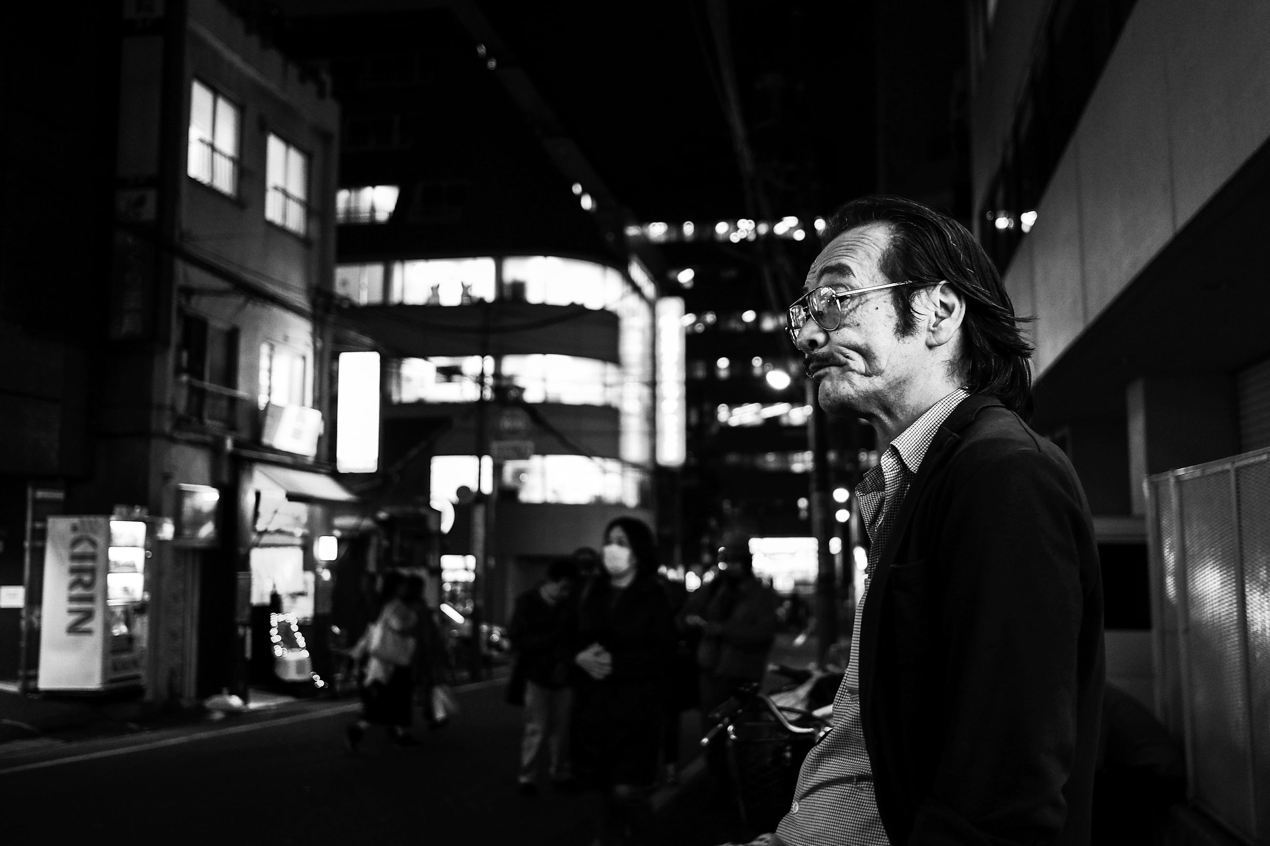 real people, lifestyles, leisure activity, young adult, young men, one person, focus on foreground, incidental people, illuminated, men, standing, architecture, night, glasses, eyeglasses, adult, casual clothing, three quarter length, side view