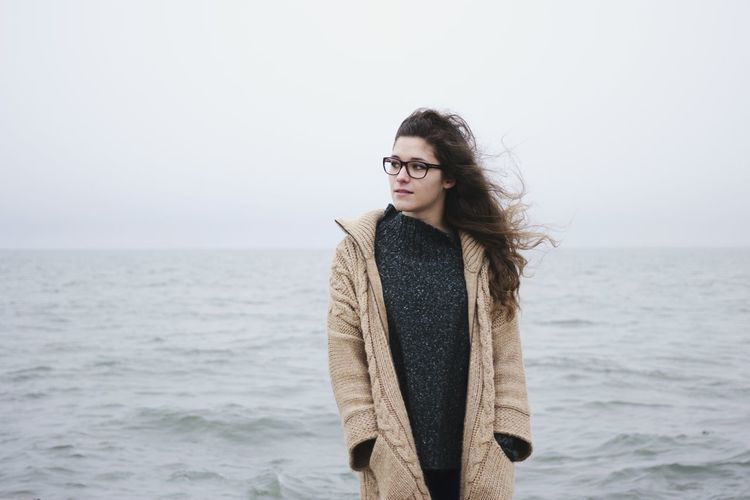 Portrait of young woman standing at seaside against sky