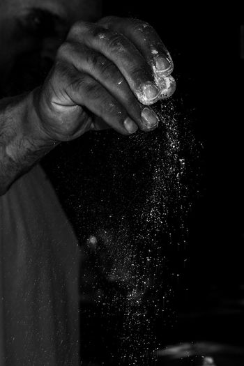 Close-up of man pouring flour against black background