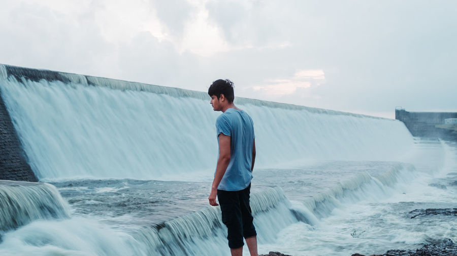 Young man looking at waterfall