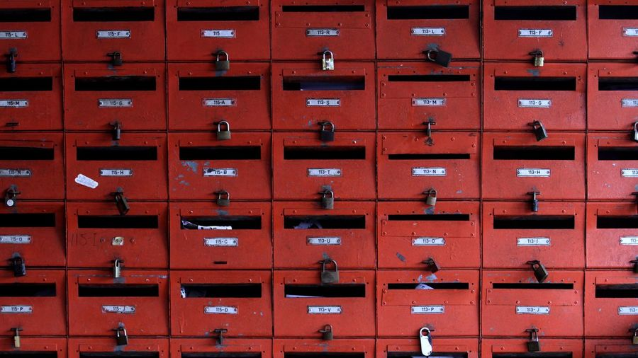 Full frame shot of closed red mailboxes at post office