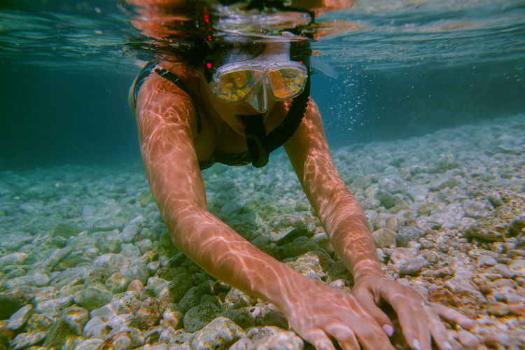 Woman snorkeling underwater. Female swimmer with diving mask and snorkel touching stones at bottom of shallow sea. Snorkeling Underwater Snorkel Snorkelling Water Sea One Person UnderSea Real People Underwater Diving Sea Life Aquatic Sport Woman Female Goggles Reflection Summer Ocean Mask Turquoise Water Vacation Sport Nature Leisure Activity Dive
