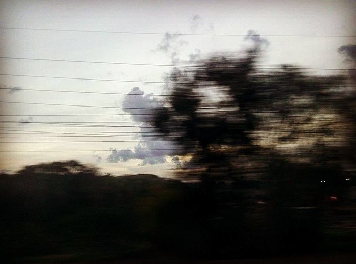 Silhouette of electricity pylon against sky