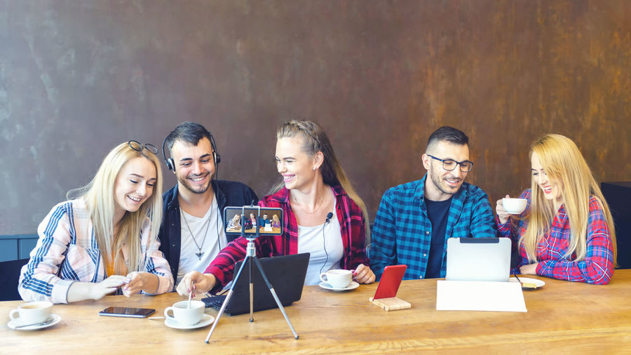 Group of people using phone while sitting on table