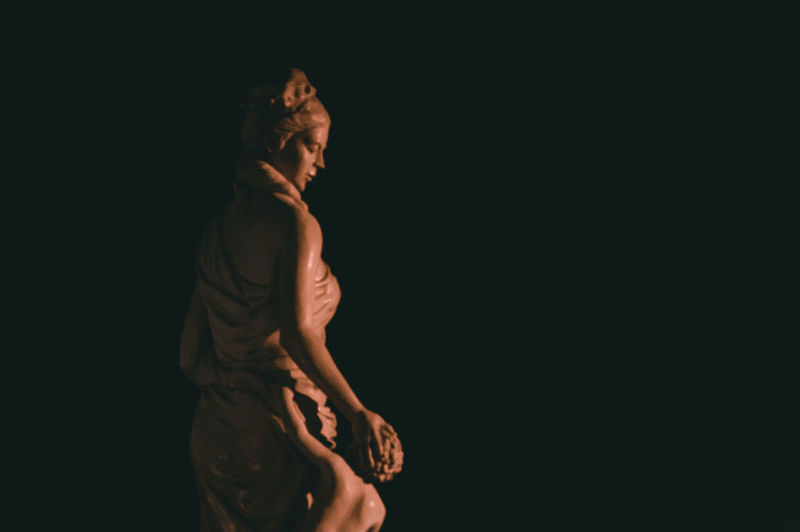 Statue against black background