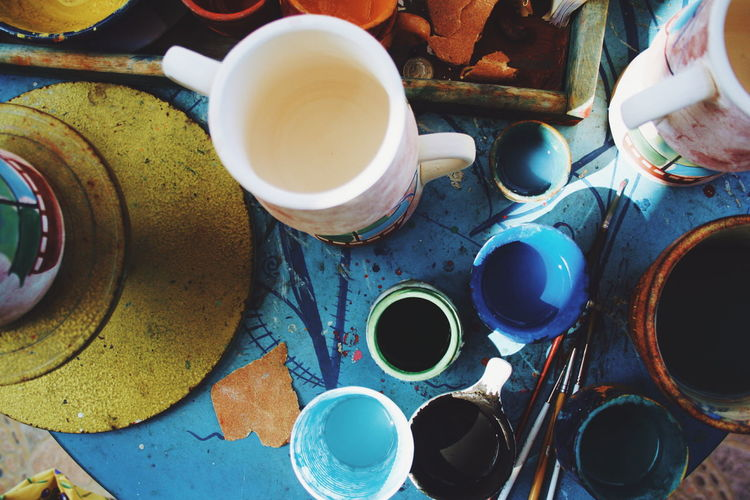 High Angle View Of Paintbrushes And Cups On Table