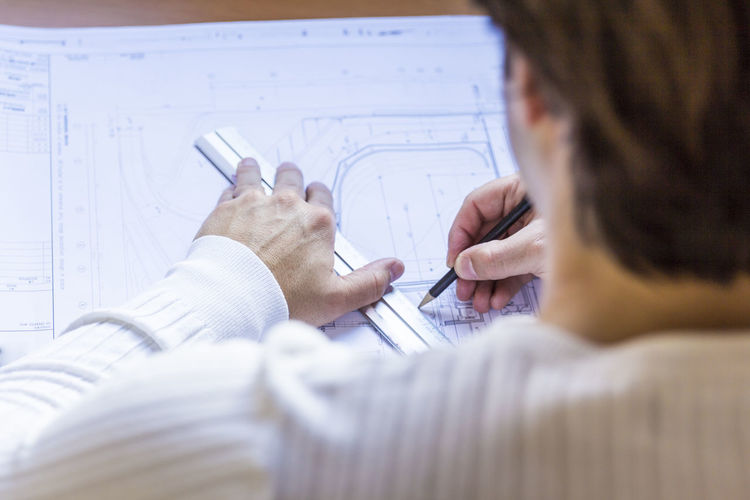 Architect working on blueprint at office