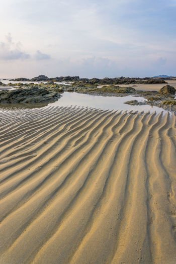 leading line on sand Beach Beauty In Nature Calm Cloud Cloud - Sky Coastline Day In A Row Natural Pattern Nature No People Non-urban Scene Remote Sand Sand Dune Sandy Scenics Sea Shore Sky Surface Level Tranquil Scene Tranquility Water Wave Pattern