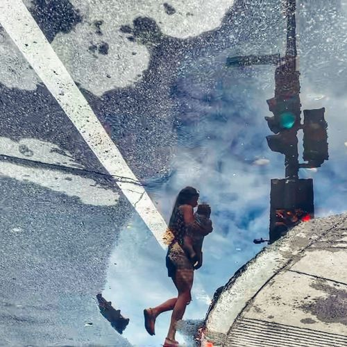High angle view of woman with umbrella standing on puddle
