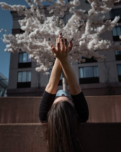 Cherry Blossom One Person Real People Leisure Activity Lifestyles Focus On Foreground Nature Building Exterior Flower Women Built Structure Architecture Hand Flowering Plant Arms Raised Plant Outdoors Body Part Casual Clothing Human Arm Day Exploring Fun Springtime Decadence The Portraitist - 2019 EyeEm Awards