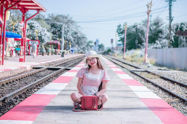 Portrait of smiling woman sitting on railroad station platform