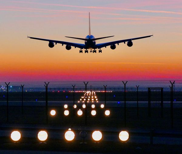 Airplane flying over runway against sky during sunset