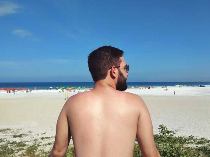 Rear view of shirtless man standing at beach against blue sky
