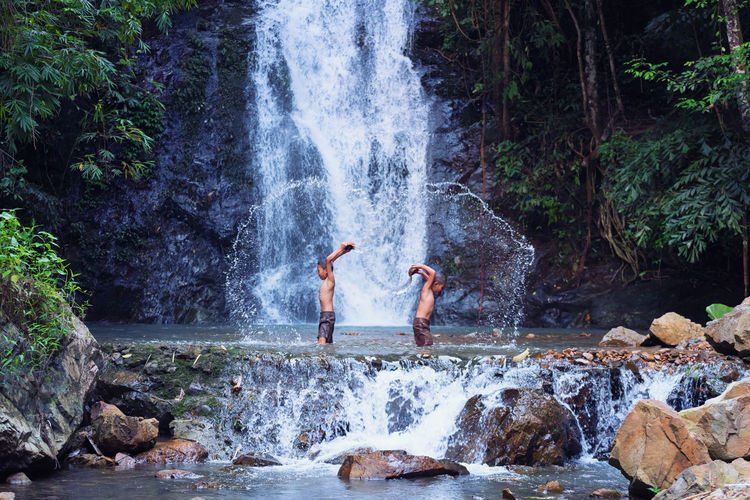 Side View Of Boys Playing In River Against Waterfall