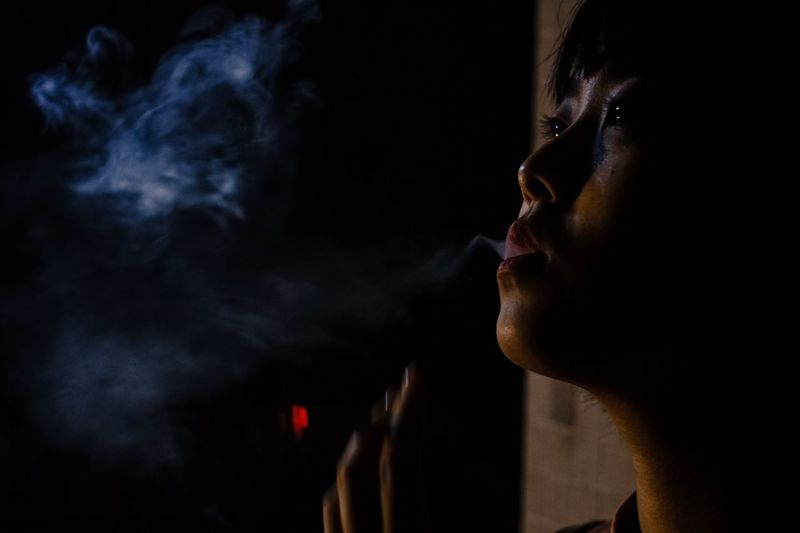 Thoughtful woman exhaling smoke at night