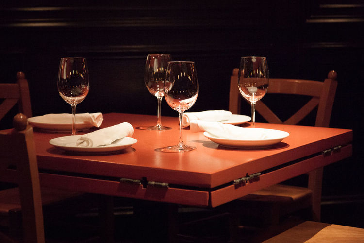 Wineglasses and plate on wooden table at restaurant