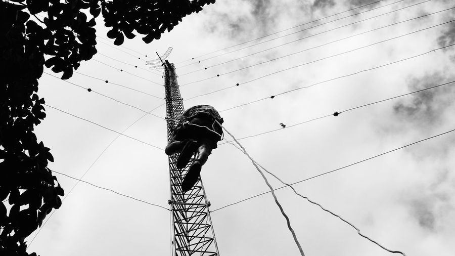 Rear view of man climbing communication tower against cloudy sky