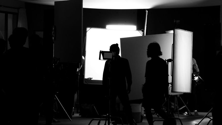 Shooting studio behind the scenes in silhouette images which film crew team working for filming movie or video with professional lighting and equipment such as camera, tripod, soft box, monitor Real People Men Silhouette Group Of People Standing Indoors  Occupation People Working Studio Business Technology Filming Day Illuminated Rear View Lighting Equipment Women Photography Themes Behind The Scenes Studio; Photo; Shoot; Photography; Photographer; Equipment; Film; Model; Fashion; Professional; Behind; Shooting; Background; Camera; Photoshoot; People; Tv; Production; Lighting; Product; Scenes; Set; Woman; Light; Video; Black; Movie; Photograph; Scene; Crew; Making; Digital; Creative; Technology; Silhouette; Videographer; Backstage; Photographic; Shadow; Team; Vdo; Soft Box; Monitor; Tripod; B-roll; Commercial; Advertising; Online
