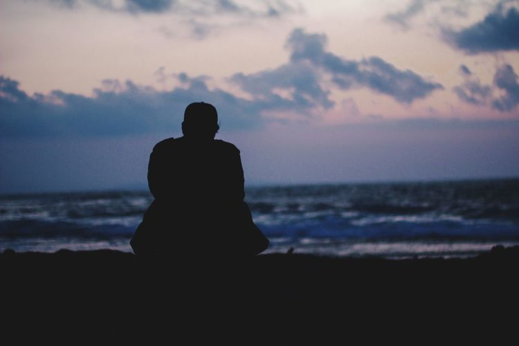 Silhouette man sitting on beach against sky during sunset
