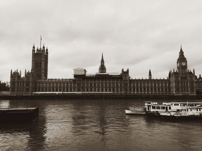 House of parliament in front of thames river against sky at dusk