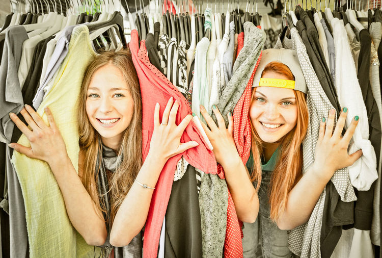 Portrait Of Smiling Young Women Hiding In Clothes Rack At Store
