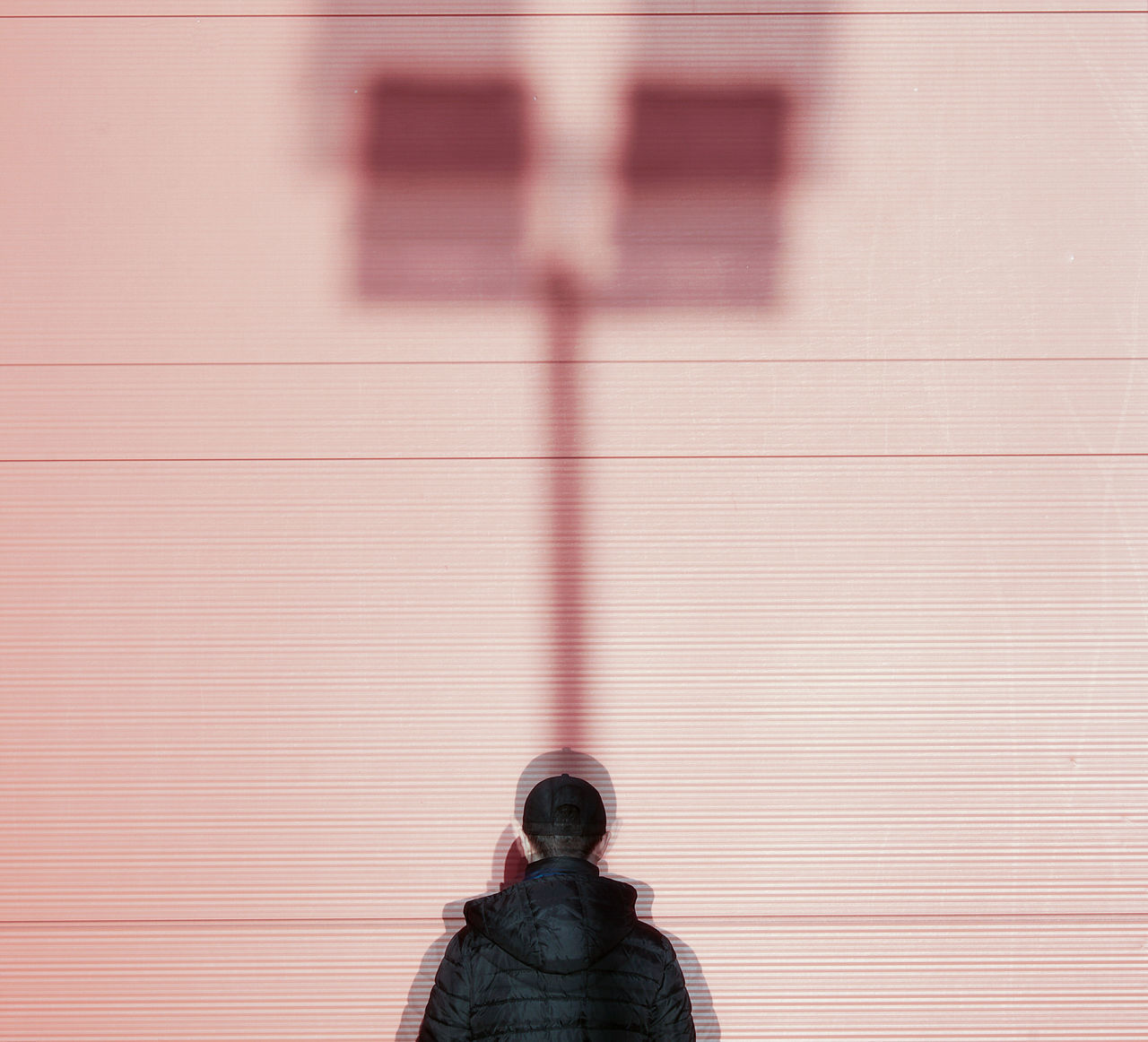 Rear View Of Man Standing Against Wall