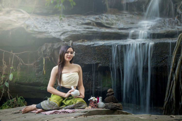 Portrait of smiling young woman sitting on rock against waterfall