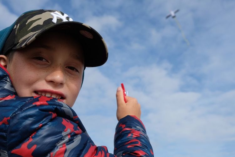 Low Angle Portrait Of Boy Flying Kite Against Sky