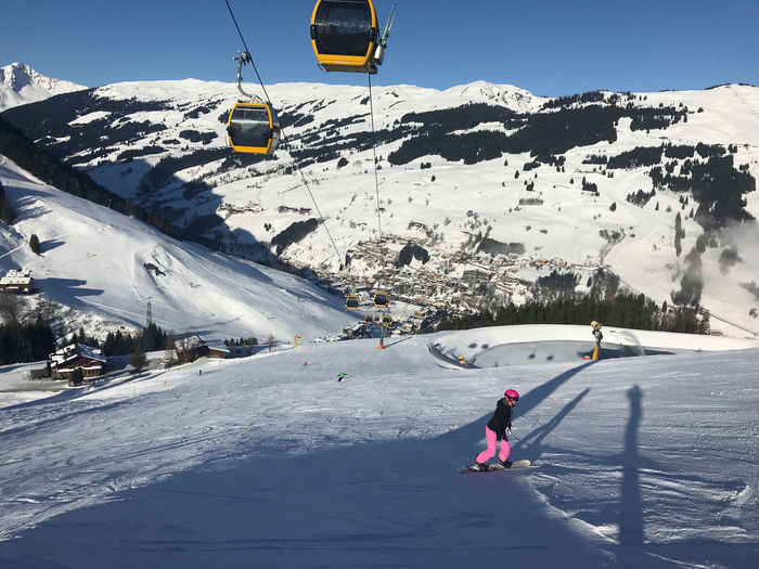Woman snowboarding on snowcapped mountain