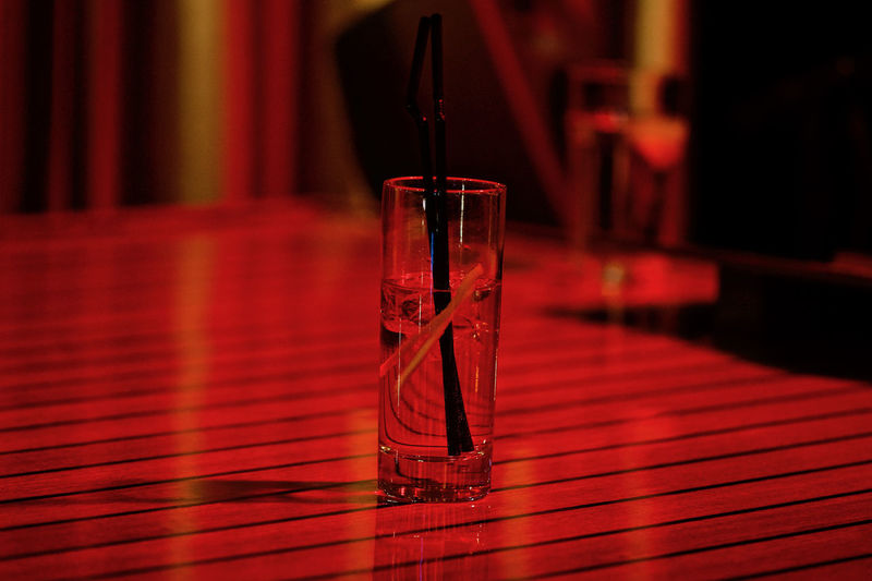 Close-up of long drink on table in red light