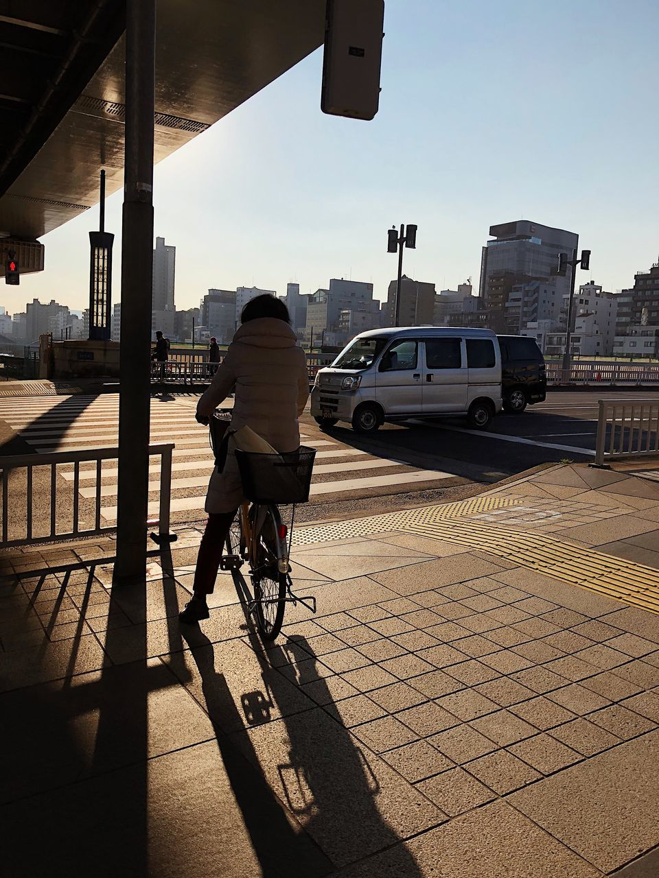REAR VIEW OF PERSON RIDING BICYCLE ON CITY