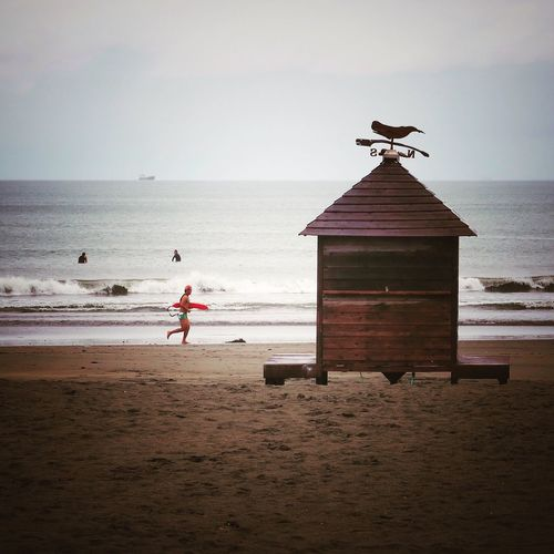 Weather Vane On Hut At Beach Against Sky