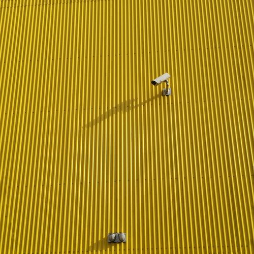 Low angle view of security camera on yellow patterned wall during sunny day