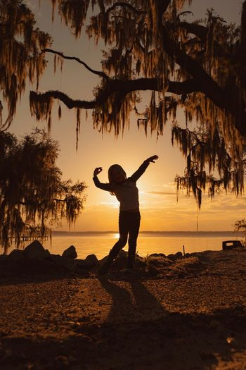 Silhouette girl dancing at beach against sky during sunset
