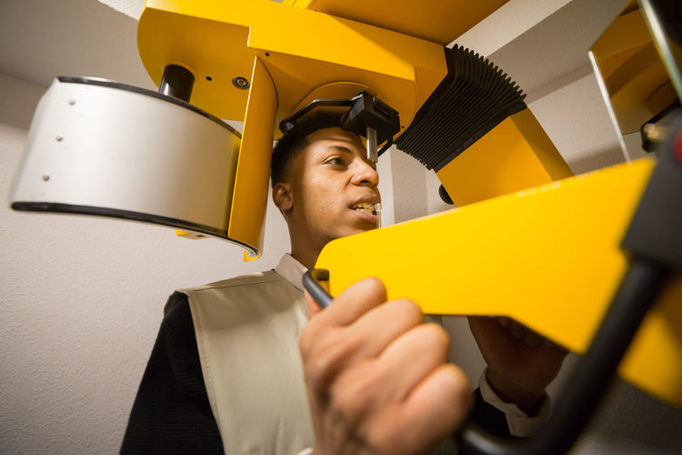 Close-Up Of Young Man Using Machinery