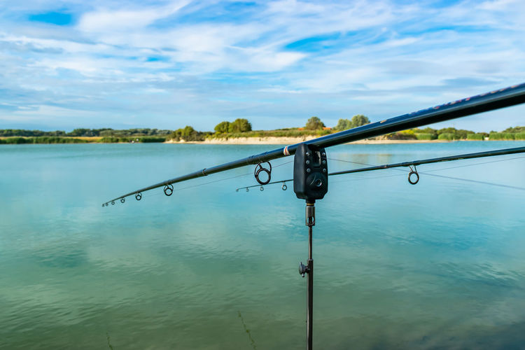 Fishing rod by lake against sky