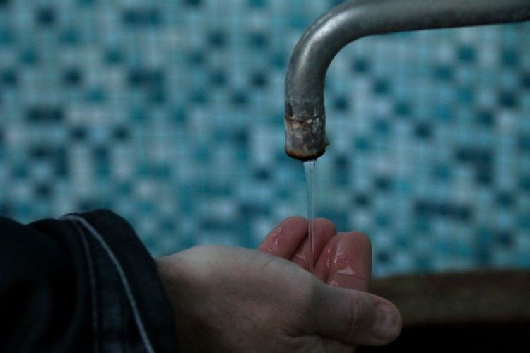 Close-Up Of Water From Faucet Falling On Cropped Hand
