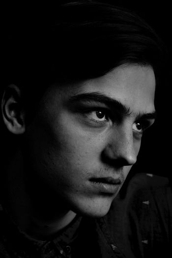 Close-up of thoughtful man against black background