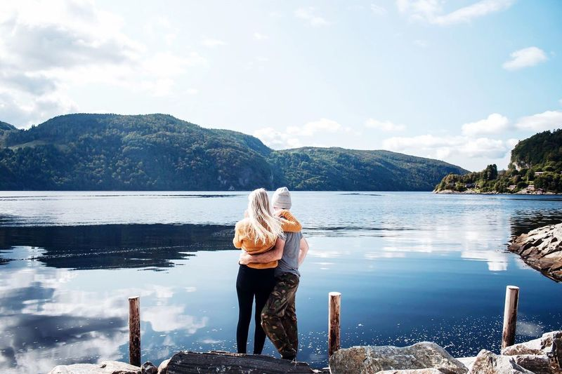 Rear view of couple looking at lake against mountain