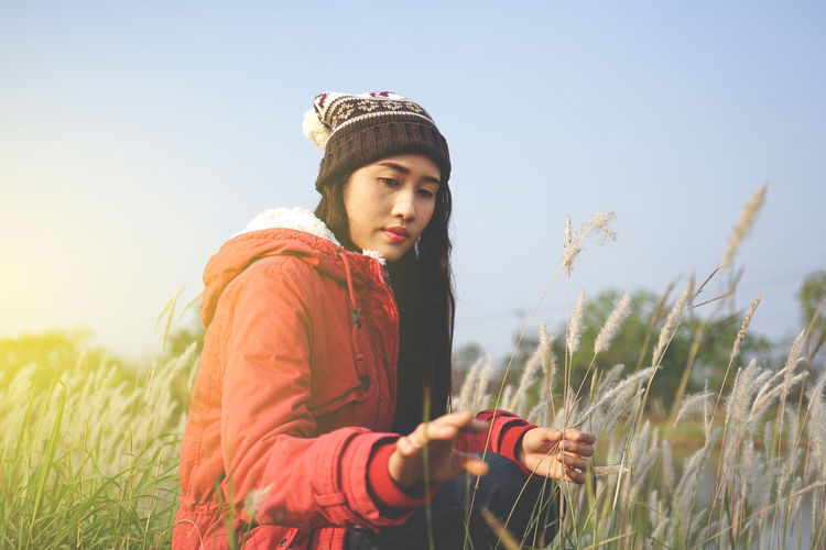 Side view of young woman crouching on grassy field against clear sky