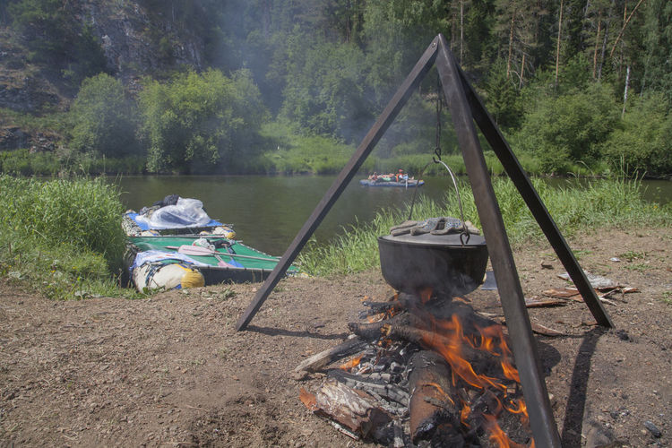 Camping Stove Hanging Over Bonfire Against River At Forest