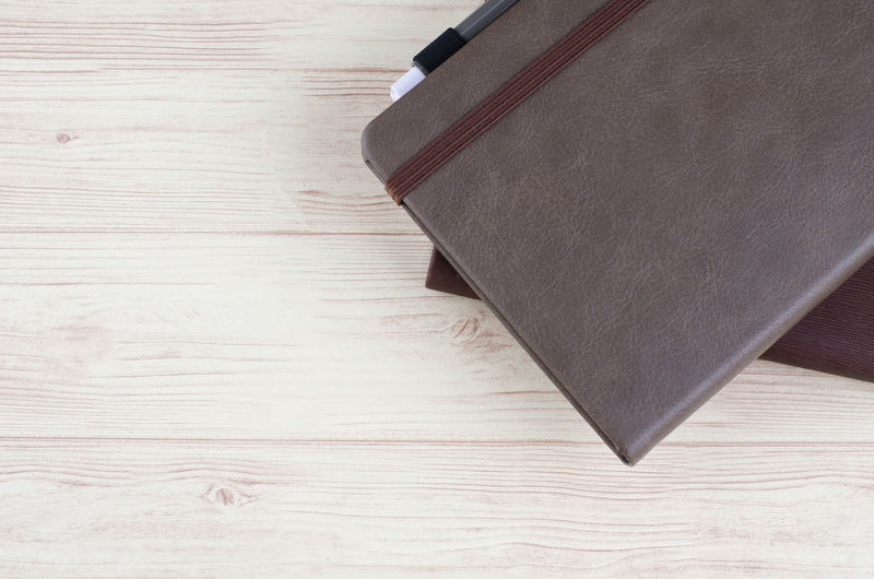 Mockup closed diary with pen on wooden background Wood - Material Indoors  No People High Angle View Still Life Table Wood Close-up Directly Above Book Publication Black Color Brown Education Leather Flooring Wood Grain Pattern Writing Instrument Hardwood Floor Hardcover Book Blank