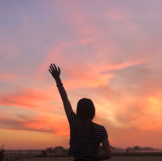Rear view of woman waving hand while standing against sky during sunset