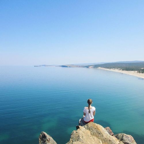 Woman Sitting On Rock Over Sea