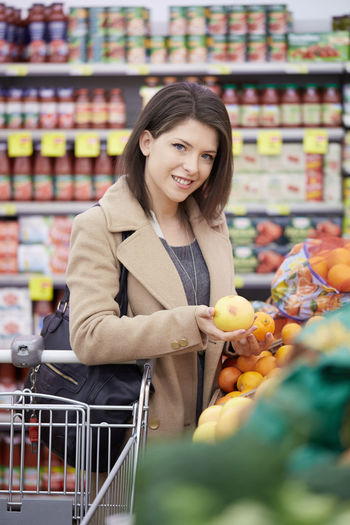 Portrait Of Smiling Young Woman Buying Fruits In Store