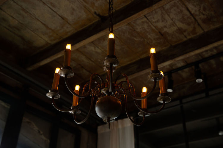 Low angle view of electric lamp hanging in ceiling