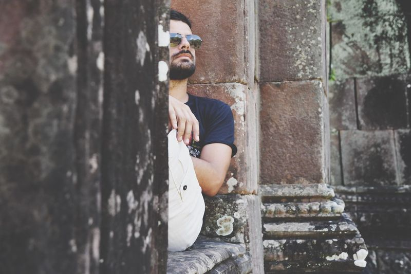 Thoughtful handsome man sitting on old ruin building wall